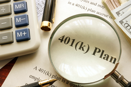 magnifying glass on top of a 401(k) plan paperwork with calculator