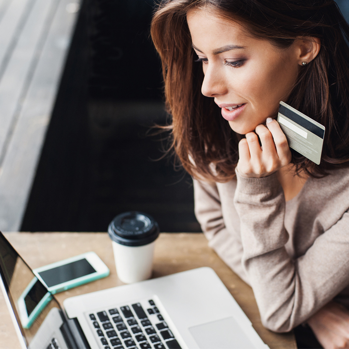 woman holding credit card and looking at computer screen