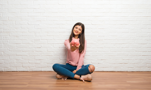 teen sitting against a white wall holding a piggy bank out in front